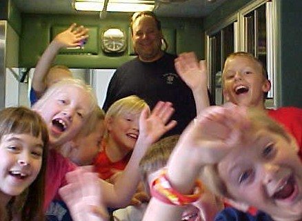 Photo of EMS employee and children waving to the camera