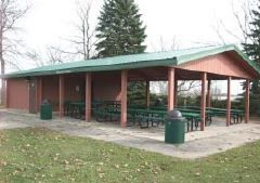 Park shelter with picnic tables in a wooded area