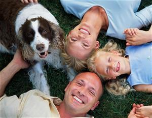 A family and a dog laying in the grass