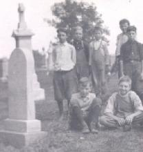 Black and white photo of boys in a cemetery