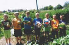 Community Garden Kids posing with vegetables